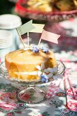 Cake decorated with paper flags and edible flowers on cake stand