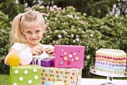A blonde girl with birthday presents and a cake in a garden