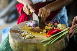 A cook cutting oriental ingredients on chopping board