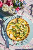 Quiche with green asparagus, ham and rocket on a table outside