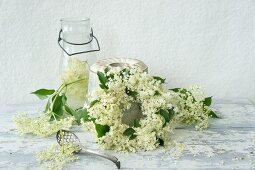 A wreath of elderflowers and a bottle of elderflower liqueur
