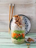 A layered oriental vegetable salad with tofu in a jar