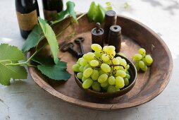 Green grapes with vine leaves and spices in a wooden dish (Italy)
