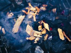 Soaked smoking chips being smoked in hot coals