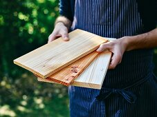 A man holding various wooden boards for grilling