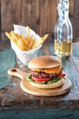 A vegan burger with tomato and cashew nut cheese in an almond coating