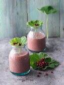 Lingonberry and fig smoothies with chia seeds, strawberries and lady's mantle leaves