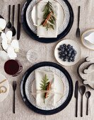 Christmas place settings with patterned plate, black cutlery and cloth napkin; Blueberries and orchid