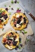 Minipizzen mit Blaubeeren, Schinken, Käse und verschiedenen Gewürzen