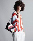 Junge Frau in längs gestreiftem Pullover mit Handtasche