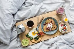 Coffee and various dishes on a wooden board on a white duvet