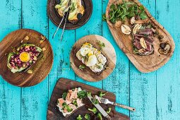 Various open sandwiches on rustic bread boards