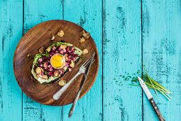 An open sandwich with a beetroot and mushroom salad and a raw egg yolk
