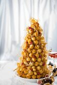 Christmas croquembouche with raspberries and figs wrapped in gold leaf