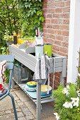 Grau lackierter Pflanztisch als Anrichte mit Thermoskannen, Kochutensilien und Geschirr auf der Terrasse