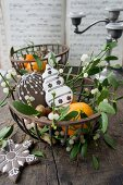 Mandarins, biscuits and nuts in a metal basket (Christmas)