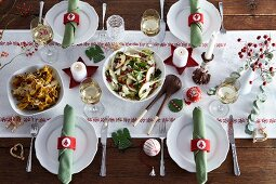 Various dishes on a table laid for Christmas dinner