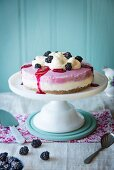 Blackberry cheesecake on a cake stand with cream and fresh blackberries