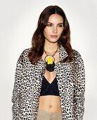 Frau in Jeans-Bustier, Jacke mit Leopardenmuster und Statementkette