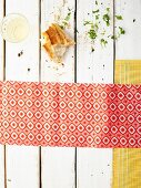 Brotstück und Weisswein auf weißem Holztisch mit gemusterter Serviette