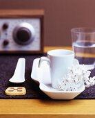 White china crockery and biscuit on dark felt mat