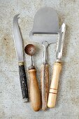 Vintage kitchen utensils: a cheese knife, a melon baller, a cheese cutter and a peeler