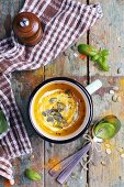Cream of pumpkin soup with pumpkin seeds on a rustic wooden table