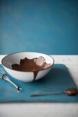 A bowl of chocolate sauce next to a spoon and a whisk