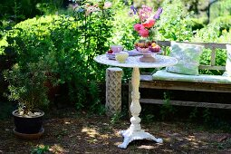 Round vintage-style garden table and wooden bench in summery garden