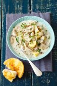 Mushroom and potato soup with cream served with gratinated bread with cheddar cheese