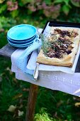 A puff pastry tart with braised radicchio and shallots on a table in a garden