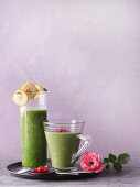 Two green smoothies garnished with pomegranate seeds and banana