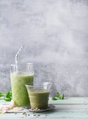 Two green smoothies garnished with rose petals and sunflower seeds
