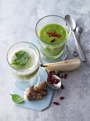 Two green smoothies garnished with spinach and goji berries
