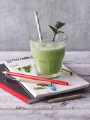 A green smoothie with a sprig of mint on school utensils
