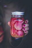 Hand hält Glas mit eingelegter Roter Bete