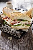 A baguette sandwich with ham, tomatoes, basil and rocket