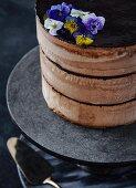 Chocolate cake with chocolate cream and edible flowers