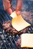 Einen Rindfleischburger mit Käse belegen