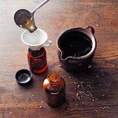 Horehound wine (à la Hildegard von Bingen) being poured into an apothecary bottle