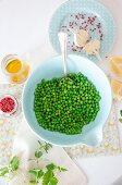Zutatenstilleben mit grünen Erbsen, rosa Pfeffer, Knoblauch, Öl und Minze