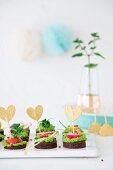 Pumpernickeltaler mit veganer Erbsen-Minzecreme dekoriert mit Herzsteckern