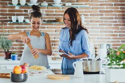 Two young women cooking pasta in a kitchen