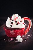 A chocolate cupcake with marshmallows and a candy cane