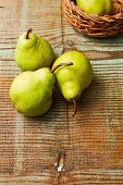 Green pears on a wooden surface and in a basket