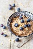 Gluten-free vegan tigernut porridge with hemp seeds, teff flakes and berries