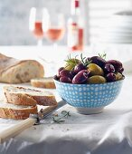 Kalamata olives and green olives with bread and rose wine on a laid table