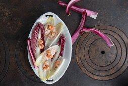 Chicoree und Radicchio mit Krebsfleisch-Mayonaise und Shrimps in Porzellanschale auf gusseisernem Herd