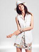 Frau in Jeanshemd, Minirock mit Stickerei und Strohhut
