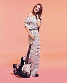Frau in Kleid mit Sternen-Print, grauer Jeansjacke und Nietengürtel